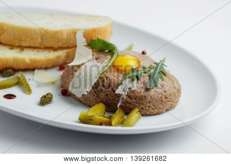 Meat Cutlet With Pickled Cucumbers, Fresh Herbs And Bread On A White Plate Closeup