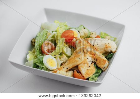 Caesar Salad With Cheese, Eggs, Herbs, Chicken, And Tomatoes In The White Plate