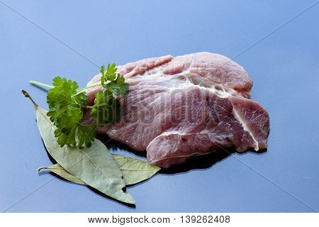 piece of raw meat and vegetables isolated on dark background