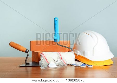 Construction tools and helmets on wooden table