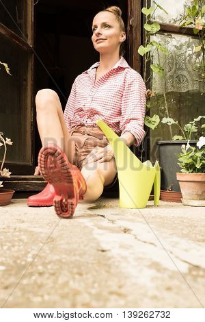 A young woman sitting at the Garden shed in her Garden.