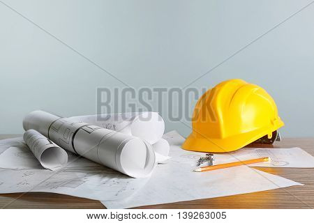 Construction blueprints with tools and helmet on light background