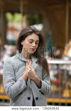 Portrait Of Melancholy Young Beautiful Brunette Woman In A Grey Coat On A Blurry Carousel Background