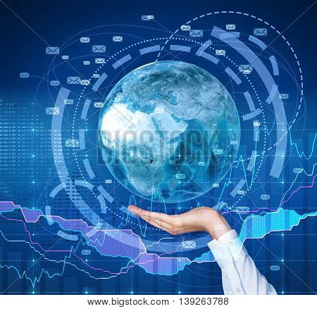 Global email marketing concept. Businessman hand holding globe with network on digital background with business chart.