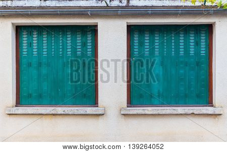 Two Big Square Windows With Green Hinged Blinds