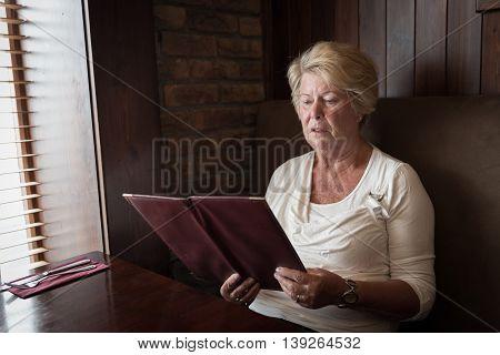 Sober Senior Woman Reading A Restaurant Menu