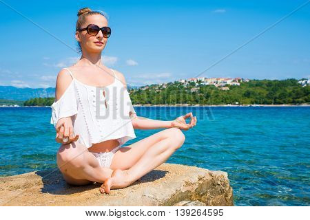 A beautiful young woman enjoying the climate in the summer meditating at the ocean.