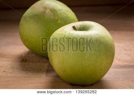 Green Granny Smith Apples on a Wood Cutting Board