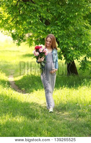 Pregnant woman with peony bouquet walking in park