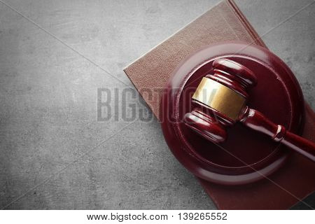Gavel with colour book on grey background