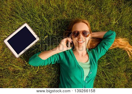 Smiling Girl Lying On Lawn With Tablet And Talking On Phone