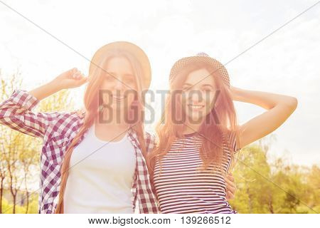 Two Positive Smiling Girls In Caps Walking In The Park And Smiling