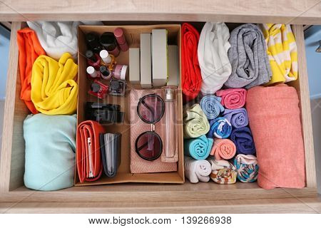Neatly folded clothes with accessories in chest of drawers