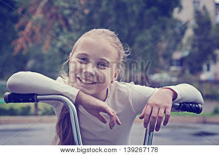 Portrait of a playful funny girl on her bike. Photos in retro style.
