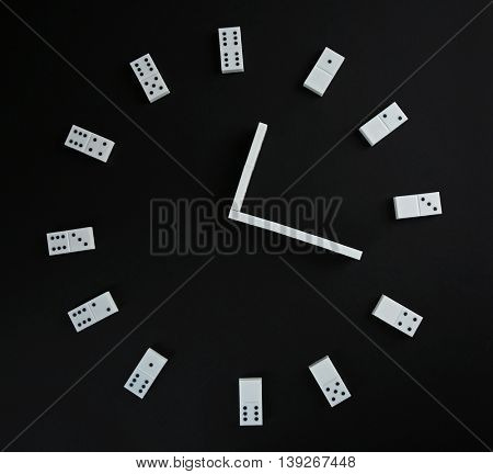 Dominoes in shape of clock on black background
