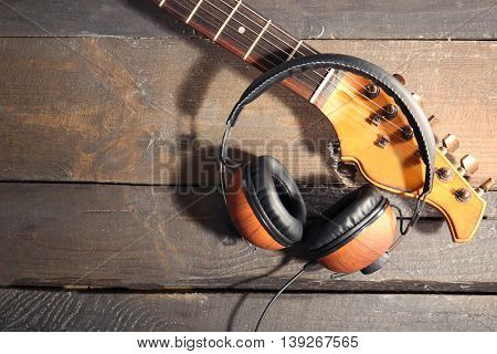 Guitar and headphones on wooden background