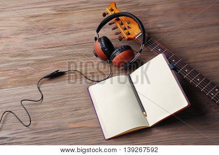 Headphones and notebook on wooden background