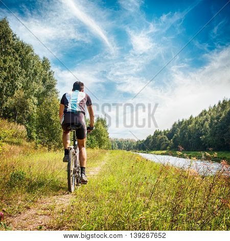 Rear View of a Young Man Riding a Bicycle on River Bank. Healthy Lifestyle Concept. Summer Leisure Activity at Nature. Square Photo with Copy Space.
