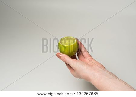 Fresh juicy tasty green lime in a Female hand on white background.