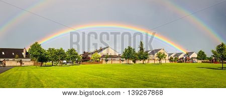 Double rainbow appears over a housing area against a dark sky in Ireland