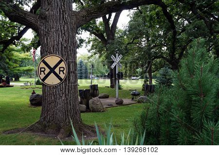 SHOREWOOD, ILLINOIS / UNITED STATES - AUGUST 30, 2015: A backyard near the Du Page River in Shorewood is decorated with railroad crossing signs.