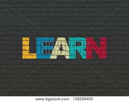 Learning concept: Painted multicolor text Learn on Black Brick wall background