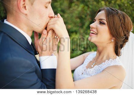 Groom kiss hand of bride at wedding