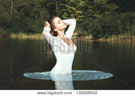 Woman in a white dress standing in water. She takes on the nature of wellness treatments.