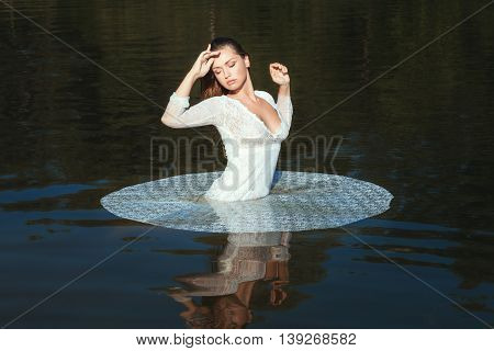 Woman in white openwork dress standing in the lake in the nature.