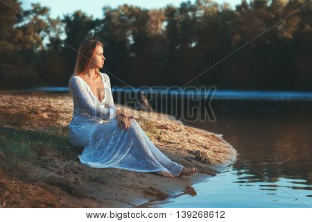 Woman sits on the lake and dreams.