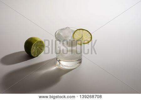 lemonade with ice and fresh slice lime on white background.