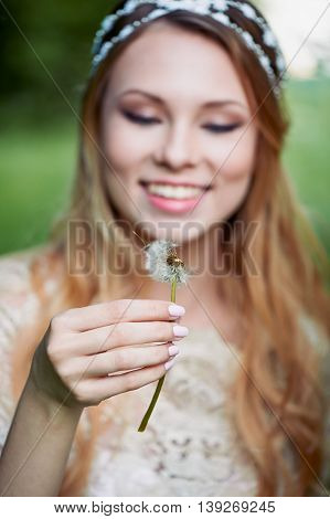Girl blowing on a dandelion, ease and tenderness. the smile on the face