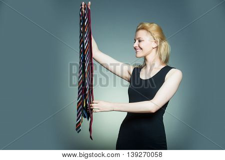 Young fashionable woman with pretty smiling face and stylish blonde hair holding many different colorful ties in hand posing on gray studio background