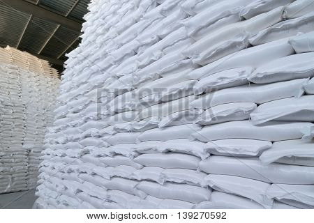 Many new plastic white sacks with goods are in big warehouse