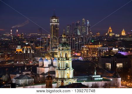 Gate bell tower of church of St. Sergius of Radonezh of Novospassky Monastery and high buildings in Moscow, Russia at night