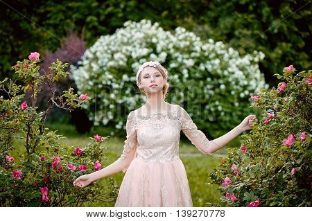 Pretty young tender blonde in a lace cream dress against the background of a blooming garden