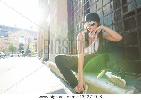 A beautiful young Hip Hop Rapper girl with Headphones in a urban environment.