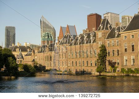 Part of the Dutch Parliament Building and Hofvijver with fountain at the Binnenhof the Hague the Netherlands. In the Background the Skyline of the Hague is visible with Skyscrapers