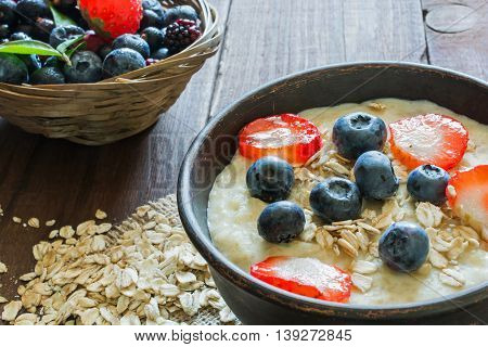 Oatmeal porridge in brown ceramic bowl with ripe berries raspberries and blueberries in wicker bowl