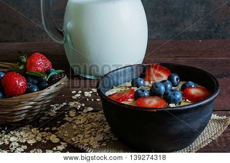 Milk in a jug and oatmeal porridge in a pottery bowl with fresh ripe berries in a wicker bowl standing on canvas on wooden table. healthy breakfast