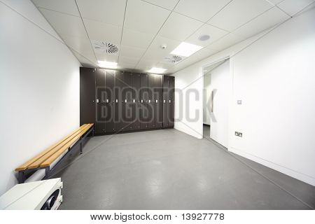 large clean locker room, gray floor and ceiling, black closet, bench near wall