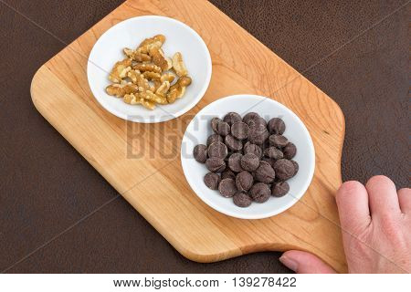 Hand holding cutting board with walnuts, and chocolate chips laid out to make a tasty treat