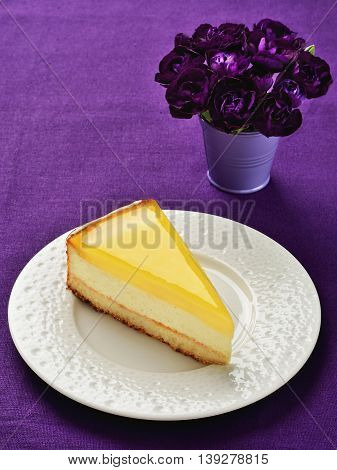 Lemon cheesecake slice on plate. Purple linen background.