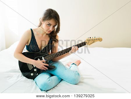 girl holding a guitar like a rock star and enjoying playing music at her room