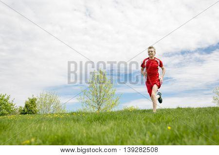 A teen boy run outside in a day light
