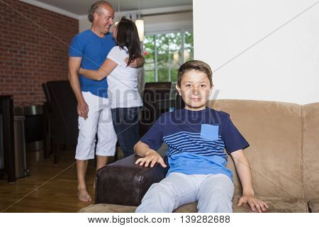 A boy sitting in couch at home, parents in background