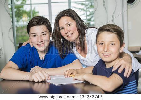 A Mother Helping Son With Homework At Table