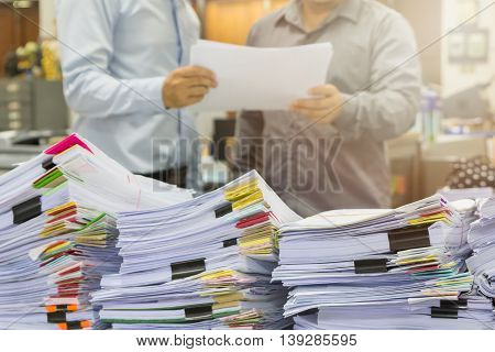 Pile Of Unfinished Documents On Office Desk With Businessman Background
