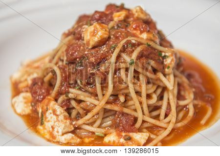Chicken spaghetti with tomato sauce on white plate
