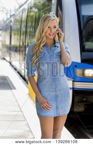 A blonde model using a cellphone as she waits for a train in a city environment